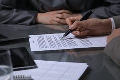 Группа в составе бизнесмены и юристы обсуждая контракт сидя на таблице Вождь женщины принимает ручку для подписания Стоковое Изображение RF