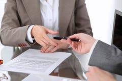 Группа в составе бизнесмены и юристы обсуждая контракт сидя на таблице Вождь женщины принимает ручку для подписания Стоковые Фото