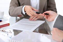 Группа в составе бизнесмены и юристы обсуждая контракт сидя на таблице Вождь женщины принимает ручку для подписания Стоковая Фотография