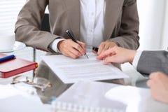 Группа в составе бизнесмены и юристы обсуждая контракт сидя на таблице Вождь женщины подписывает бумаги Стоковая Фотография RF