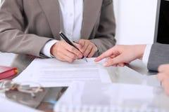 Группа в составе бизнесмены и юристы обсуждая контракт сидя на таблице Вождь женщины подписывает бумаги Стоковая Фотография