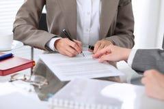 Группа в составе бизнесмены и юристы обсуждая контракт сидя на таблице Вождь женщины подписывает бумаги Стоковые Изображения RF