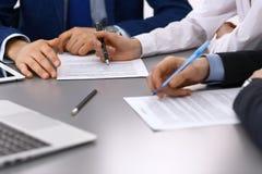 Группа в составе бизнесмены и юрист обсуждая контракт завертывает сидеть в бумагу на таблице, крупный план Бизнесмен подписывает стоковое фото rf