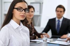 Группа в составе бизнесмены на встрече на предпосылке офиса Фокус на красивом брюнет Стоковое Изображение RF