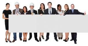Группа в составе бизнесмены представляя пустое знамя Стоковое Фото