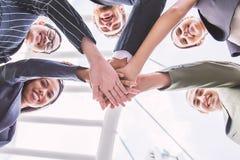 Группа в составе бизнесмены при их руки держа совместно, знамя сыгранности дела Стоковые Фото