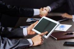 Группа в составе бизнесмены работая с цифровой таблеткой Стоковые Изображения