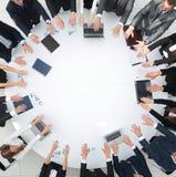 Группа в составе бизнесмены сидя на круглом столе, и кладя его ладони на таблицу Стоковые Изображения