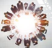 Группа в составе бизнесмены сидя на круглом столе, и кладя его ладони на таблицу Стоковое фото RF