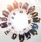 Группа в составе бизнесмены сидя на круглом столе, и кладя его ладони на таблицу Стоковое Фото