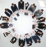 Группа в составе бизнесмены сидя на круглом столе, и кладя его ладони на таблицу Стоковые Изображения RF