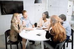 Группа в составе бизнесмены сидя на столе Стоковые Изображения