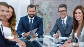 Группа в составе бизнесмены сидя на столе стоковая фотография rf
