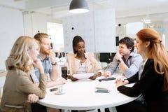 Группа в составе бизнесмены сидя на столе Стоковое Изображение RF