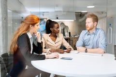 Группа в составе бизнесмены сидя на столе Стоковые Изображения RF