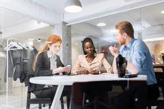 Группа в составе бизнесмены сидя на столе Стоковое Изображение