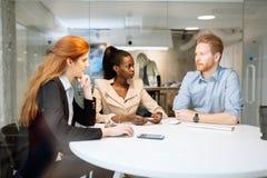 Группа в составе бизнесмены сидя на столе Стоковая Фотография