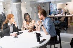 Группа в составе бизнесмены сидя на столе Стоковые Фотографии RF