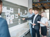 Группа в составе бизнесмены смотрит доски для различных графиков и проектов Стоковые Изображения