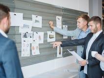 Группа в составе бизнесмены смотрит доски для различных графиков и проектов Стоковые Фотографии RF