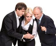Группа в составе бизнесмены смотря сотовый телефон Стоковая Фотография RF