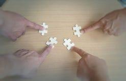 Группа в составе бизнесмены собирая мозаику хотеть положить части головоломки совместно на деревянное backgroung таблицы для supp Стоковое фото RF