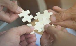 Группа в составе бизнесмены собирая мозаику хотеть положить части головоломки совместно на деревянное backgroung таблицы для supp Стоковые Изображения