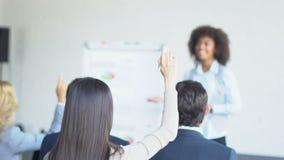 Группа в составе бизнесмены спрашивая вопрос к представлению коммерсантки ведущему в современном конференц-зале видеоматериал