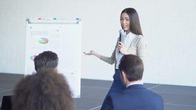 Группа в составе бизнесмены спрашивая вопрос к представлению коммерсантки ведущему обсуждая финансовый отчет видеоматериал
