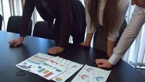 Группа в составе бизнесмены стоит вокруг замедленного движения таблицы акции видеоматериалы
