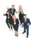 Группа в составе бизнесмены стоя совместно в офисе и показывать Стоковое Фото