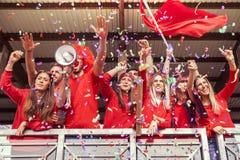 Группа в составе вентиляторы одела в красном цвете наблюдая событие спорт стоковые изображения
