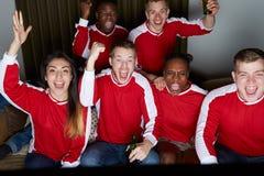 Группа в составе вентиляторы спорт смотря игру на ТВ дома Стоковая Фотография RF