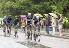 Группа в составе велосипедисты ехать в дожде - Тур-де-Франс 2014 Стоковая Фотография