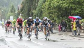 Группа в составе велосипедисты ехать в дожде - Тур-де-Франс 2014 Стоковое фото RF