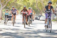 Группа в составе велосипедисты на пригородной улице Стоковое фото RF