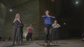 Группа в составе взрослая середина постарела женщины делая тренировки йоги после их инструктора пока размышляющ в солевом руднике акции видеоматериалы