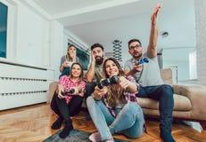 Группа в составе видеоигры игры друзей совместно дома Стоковые Изображения RF