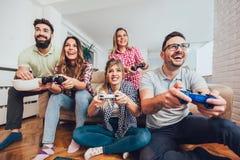 Группа в составе видеоигры игры друзей совместно дома Стоковые Фото