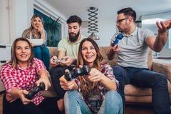 Группа в составе видеоигры игры друзей совместно дома Стоковое Изображение RF