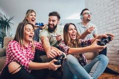 Группа в составе видеоигры игры друзей совместно дома Стоковое Изображение