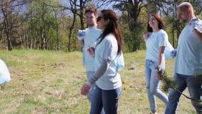 Группа в составе волонтеры с сумками отброса в парке видеоматериал