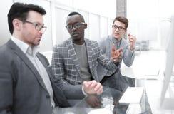 Группа в составе вскользь одетые предприниматели обсуждая идеи в офисе стоковые фотографии rf