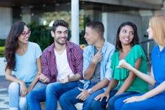 Группа в составе говорить молодым взрослым людям и женщине стоковые фото