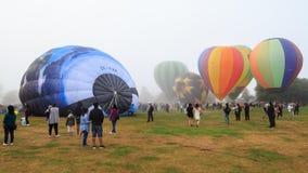 Группа в составе горячие воздушные шары на раздувая фестивале, положенная в кожух в туман стоковые изображения