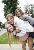 Группа в составе девочка-подростки играя и усмехаясь совместно outdoors стоковая фотография