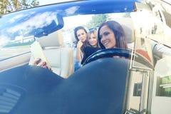 Группа в составе девушки имея потеху в автомобиле и принимая selfies с камерой Стоковое фото RF