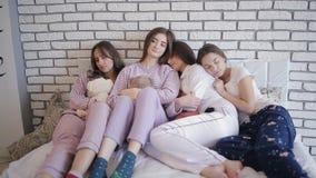 Группа в составе девушки в их пижамах спать в кровати после партии сток-видео