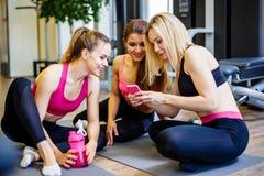 Группа в составе девушки в классе фитнеса смотря smartphone и усмехаться Женские друзья в спортзале принимая пролом от разминки и Стоковое Изображение