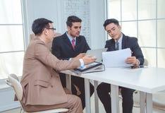 Группа в составе деловые партнеры анализируя и обсуждая во время wor Стоковое Изображение RF